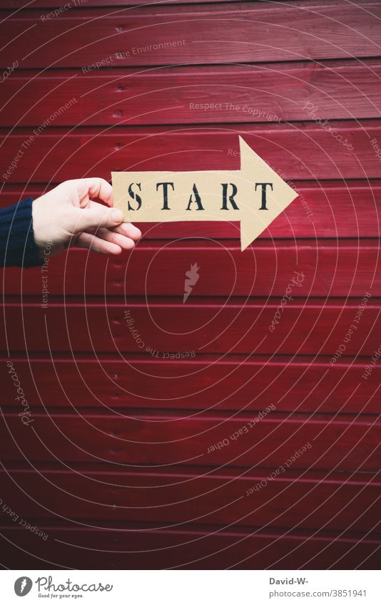 Start printed on an arrow is held by one hand launch Arrow Hand Beginning loose start Sign Direction Success Forwards Career