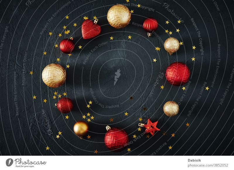 Christmas composition. Round frame of red and golden Christmas baubles and festive ribbons on dark background, top view Decoration Composition of the creatively