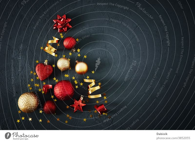 Christmas tree made of red and golden baubles and festive ribbons on dark background with copy space. Christmas concept christmas decoration creative card