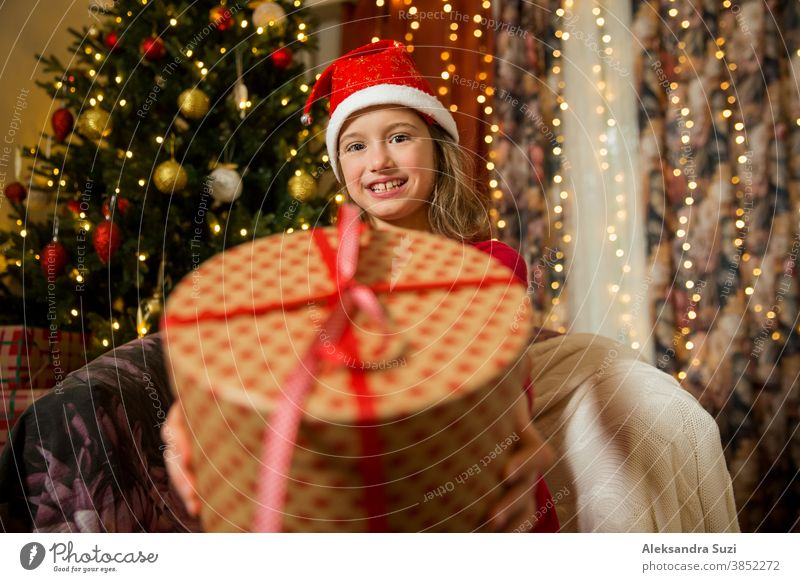 A happy child in red Santa hat is celebrating Christmas. Cute girl holding wrapped gift, smiling and waving hand, sitting in decorated with Christmas lights and tree room. Happy holidays