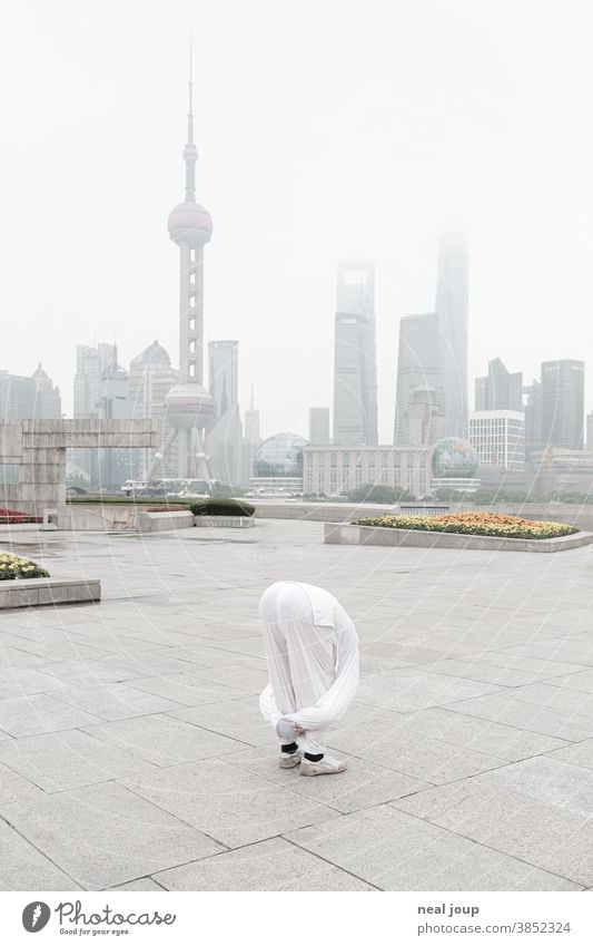 Yoga pose in front of the skyline of Shanghai prevention Acrobatic Skyline China Tourist Attraction Pu Dong Deserted in the morning foggy Moody tranquillity