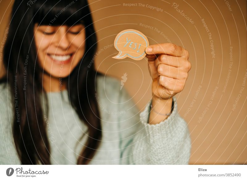 "Laughing woman holding a speech bubble with the word ""yes"" in English Yes Laughter Positive Affirmative Joy Good mood Success successful feeling of happiness"