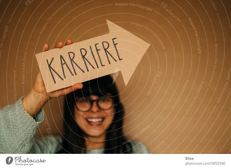 Laughing woman holds an arrow with the word career on it. Career Profession working life training Ambitious Business Work and employment Arrow Orientation