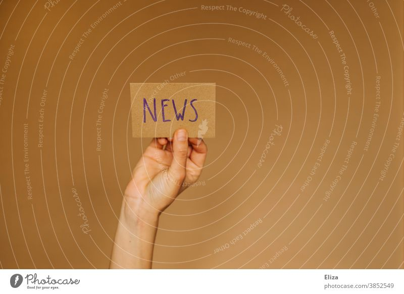 Hand holds up a sign saying News. Concept News, Newsletter, News. news English News & Events Information Journalism Print media Media Press message transmission