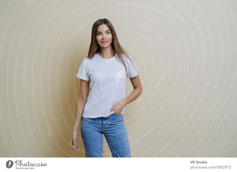 Studio shot of pretty slim woman keeps hand in pocket, wears casual t shirt and jeans, stands in relaxed pose, looks at camera self confident, isolated over beige background talks casually with client