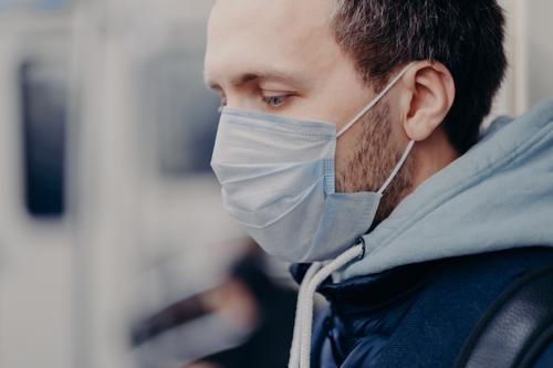 Close up shot of serious man walks in crowded places, commutes to work in underground, wears medical mask for face protection during outbreak and coronavirus infection. Disease protection concept