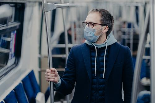 Prevention in public transport, health awareness for pandemic protection. Young man wears medical mask while travels by urban train, protects himself from virus. Covid-19 outbreak in Europe.