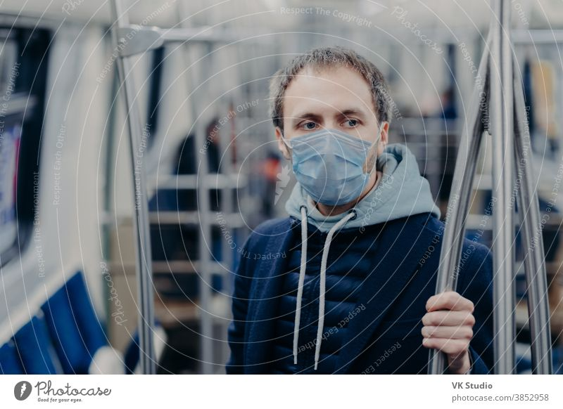 Photo of male passenger wears face mask while travels by subway during infectious disease, prevents spreading coronavirus, poses in public transport, thinks about epidemic situation in his country
