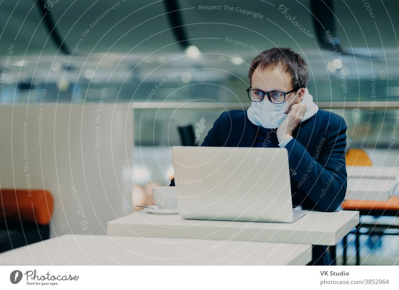 Photo of serious man concentrated in screen of laptop computer, works from distance during coronavirus outbreak, wears protective mask not to spread disease, drinks coffee, sits at white table