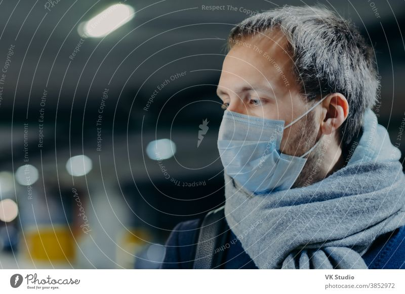 Pensive man wears protective mask against new coronavirus from China, wrapped scarf around neck, looks somewhere, thinks about epidemic situation. Influenza, flu symptoms, virus, treatment concept