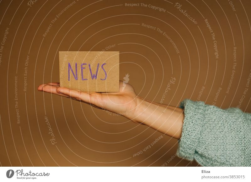 One hand presents a sign with the word news in English Reporting News & Events Newsletter Journalism Media Information Education Current Current events