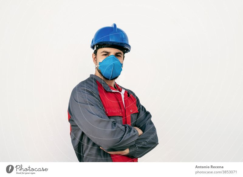 Attractive worker man with face mask for protection looks at camera covid-19 uniform security pandemic virus white background wall coronavirus surgical mask