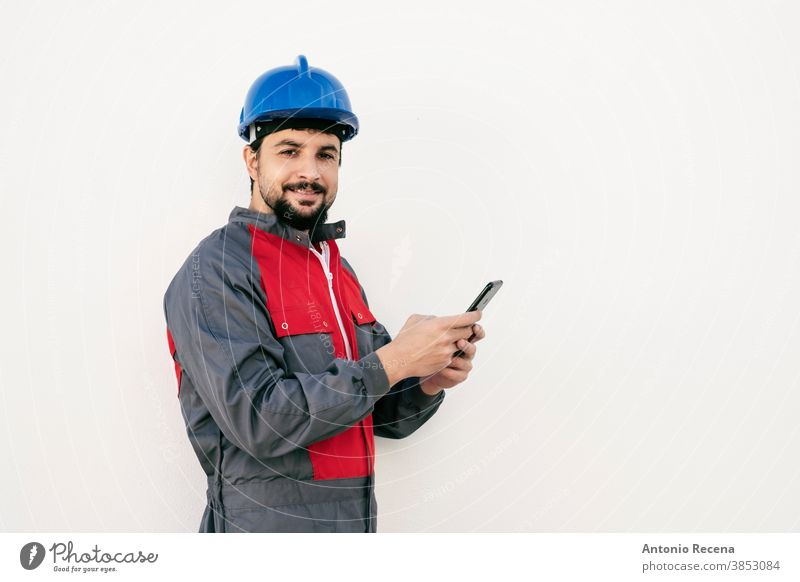 Bearded worker man with smart phone looking at camera smiling laborer uniform helmet pandemic virus white background wall hardhat protection goatee beard arab
