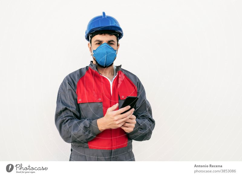 Bearded worker man with face mask looking smart phone covid-19 uniform security pandemic virus white background wall coronavirus surgical mask protection