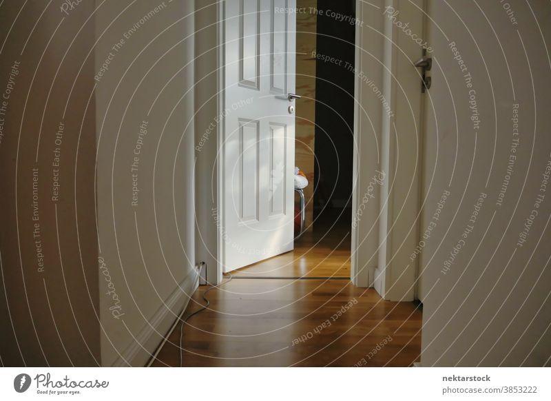 Open House Door and Corridor with Wooden Floor door home floor open opened corridor parquet wood wooden indoor inside room day natural lighting house dwelling