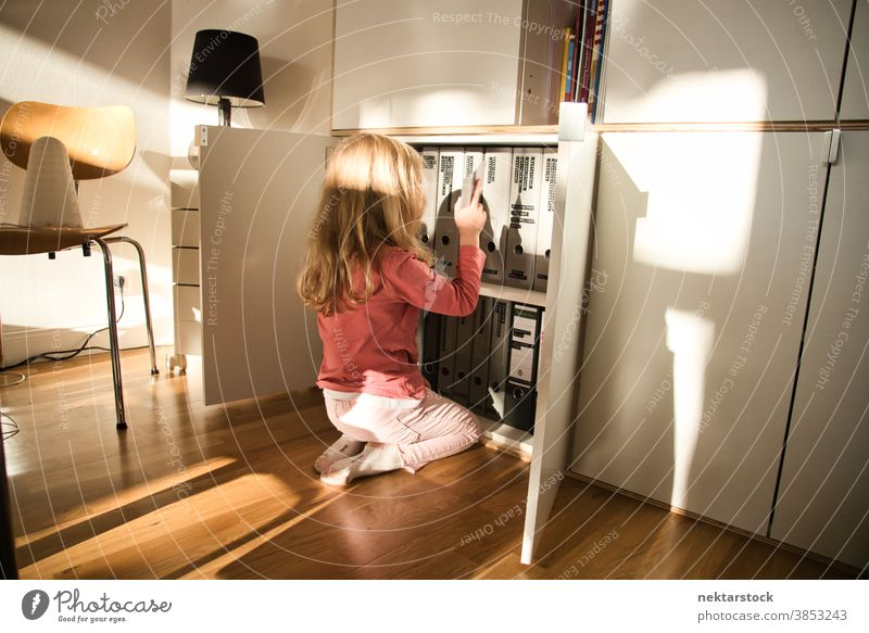 Child Kneeling Looking at Documents Folders in Closet child girl play blond caucasian lifestyle closet folder binder document rear view back turned open female
