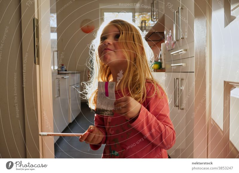 Small Caucasian Girl Holding Sign and Pencil in Home Kitchen child girl play blond caucasian lifestyle female indoor natural lighting grow learn pencil write