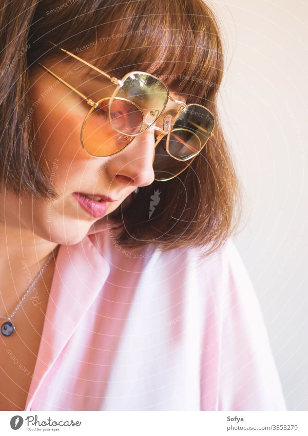Young woman in pink shirt with sunglasses young fashion accessory autumn spring transparent retro vintage girl brunette face smile fun funny lady wear hipster