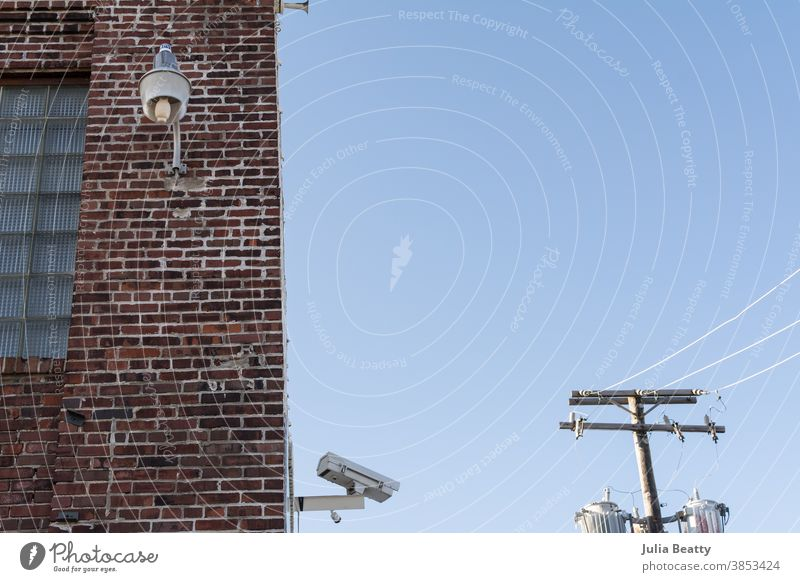Security camera, powerlines, and industrial light on brick warehouse building security big brother Surveillance Surveillance camera Monitoring monitor Safety