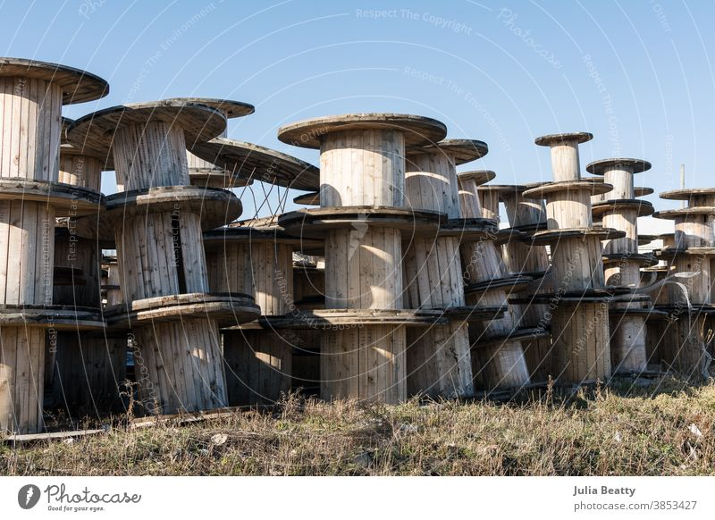 Wooden spools, cable reels, stacked up for storage in an industrial park wooden spool old pile wood slat vintage retro worn metal architecture sky container