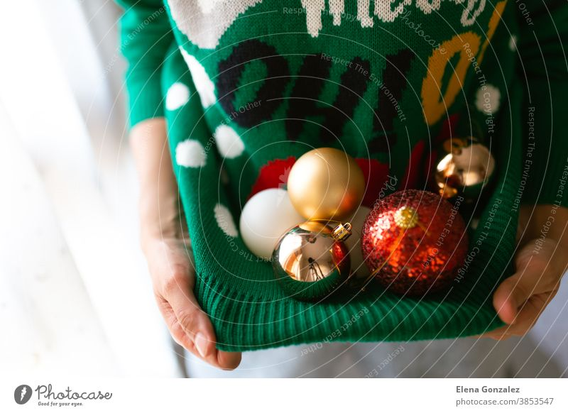 Unrecognizable woman holding Christmas tree balls in a Christmas jumper with lights christmas merry christmas new year december christmas balls women baubles