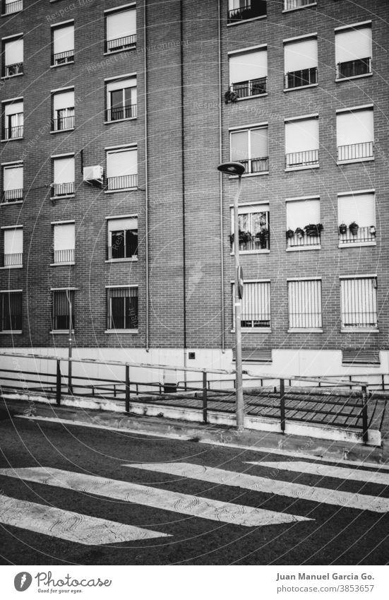 Suburban neighborhood housing block in black and white windows zebra crossing brick dwellings flats humble protection street sidewalk blinds house facade