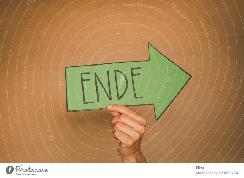 Hand holds a green arrow with the word end written on it. Separation, off, over. End Divide from Transience Green Past sign Arrow Direction Orientation