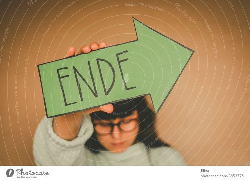 Woman holding a green arrow with the word end End over from over and done Transience Divide Past Quit Green Arrow authored Suicide Suicidal tendancy Exit route