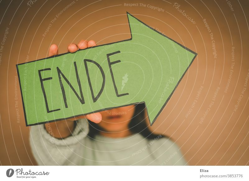 Woman holding a green arrow written on the end is End ending finite over from Come to an end Transience Divide Past Arrow Green Neutral background Way out