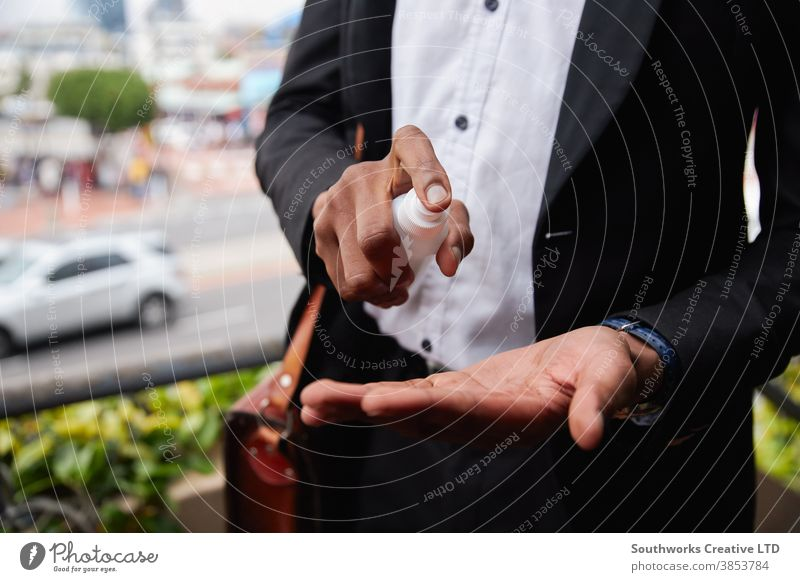 Close Up Of Businessman Spraying Hands With Sanitiser During Health Pandemic business businessman office worker sanitizer hand sanitizer sanitizing dispenser