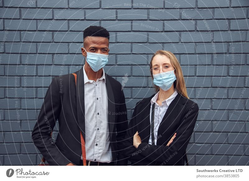 Portrait Of Business Couple Wearing Masks Standing By Wall Outside Office During Health Pandemic business businessman businesswoman face mask face covering