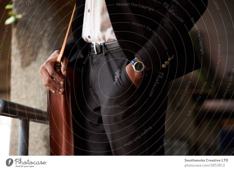 Close Up Of Businessman With Leather Bag Standing With Hand In Pocket business businessman office worker close up standing outdoors hand in pocket suit watch