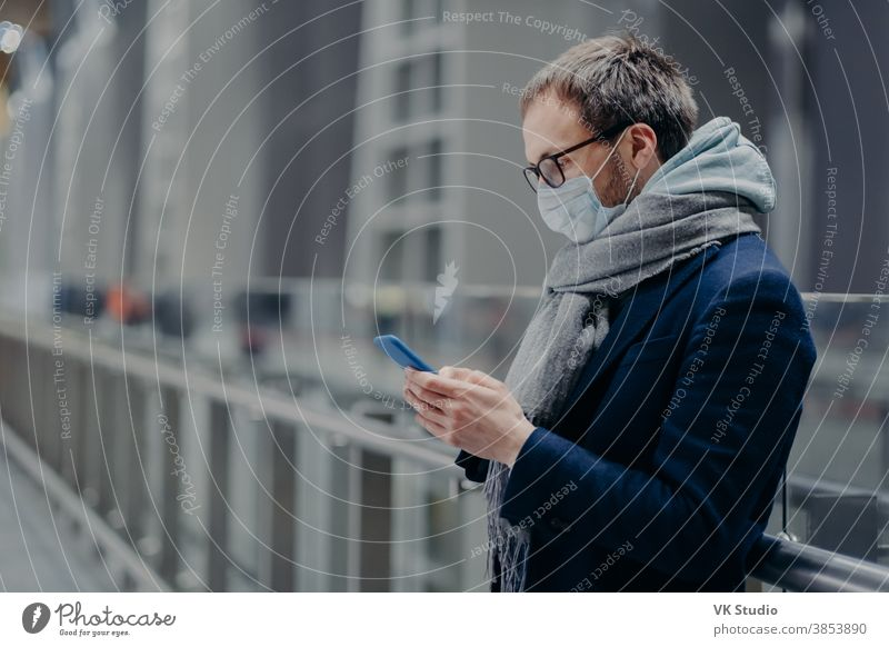 Sideways shot of male blogger sends text messages and reads comments from followers on modern cellphone, wears sterile medical mask to protect himself from coronavirus or other infectious disease