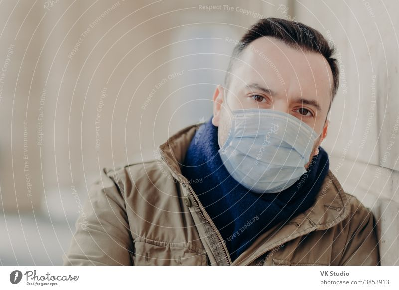 Outdoor shot of young European man has coronavirus symptoms, wears protective surgery mask, tries protect from viruses and infections, needs to see doctor. Street and air contamination problem