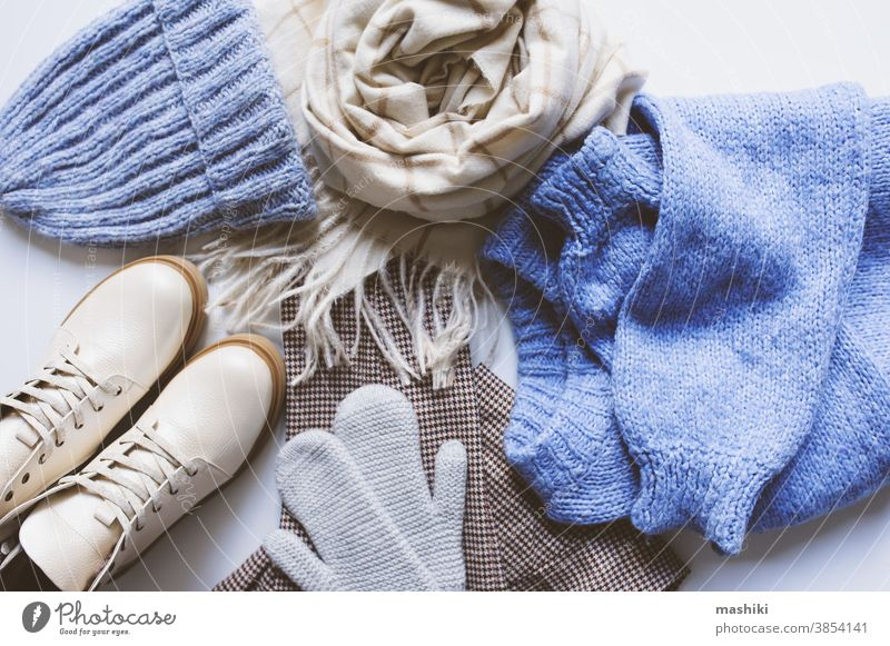 stylish modern winter or fall woman clothes set top view. Trendy shoes, sweaters and accessories in beige and blue tones with Christmas lights and autumn leaves.