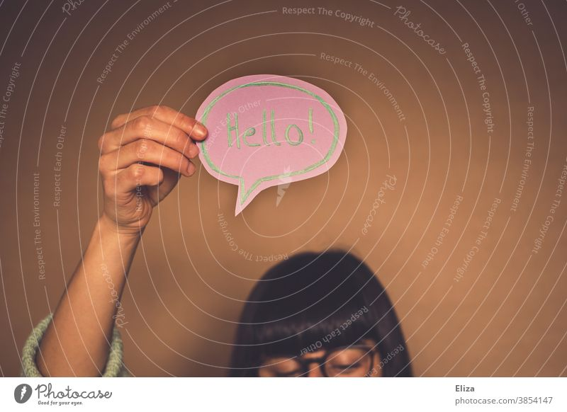 Woman with a speech bubble with hello written in English Hello Welcome Foreign language Communicate Neutral Background authored Word hello! stop attention