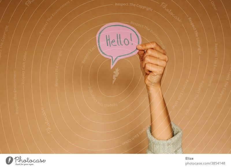 Hand holds a speech bubble in which Hello! stands. Greetings in English. salute sb. Speech bubble hello Foreign language Communicate Language communication Hi