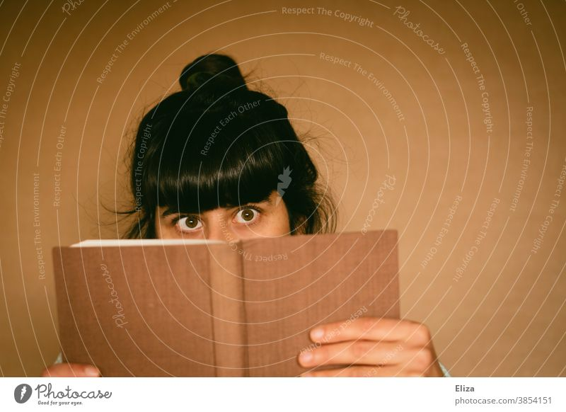 Young woman peering out from behind a book Book Reading Squint Caught Funny Reading matter inquisitorial Novel Print media Literature Brunette