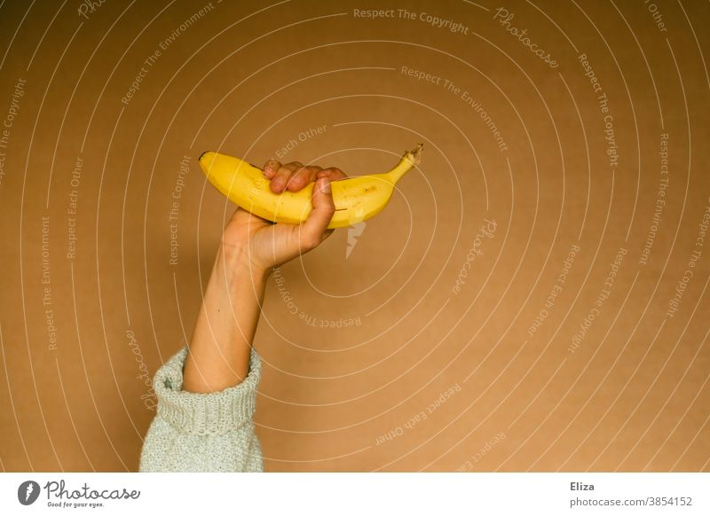 One person still holds a banana Banana Hand fruit salubriously Healthy Eating Yellow stop Woman Neutral background