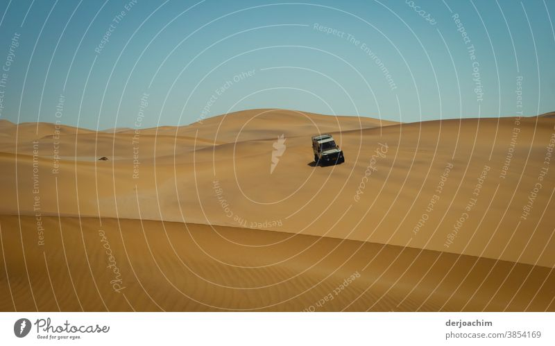 On tour in the dunes. A car drives down the sand dune. Blue sky and no clouds. Namibia Desert Africa Sand Colour photo automobile duene Landscape Nature Hot Sky