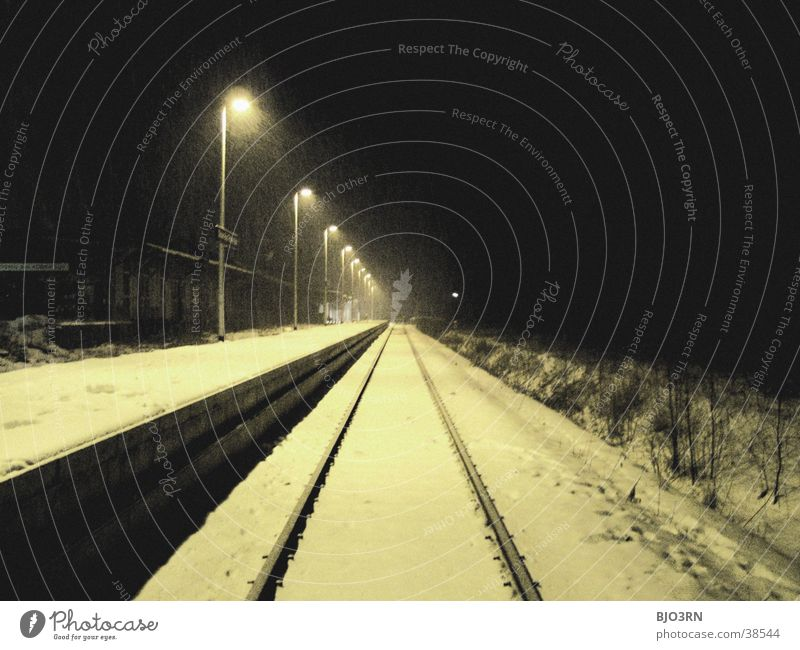 The train is coming Lamp Winter Platform Railroad tracks Night Cold Empty Transport Train station Floodlight Light Snow
