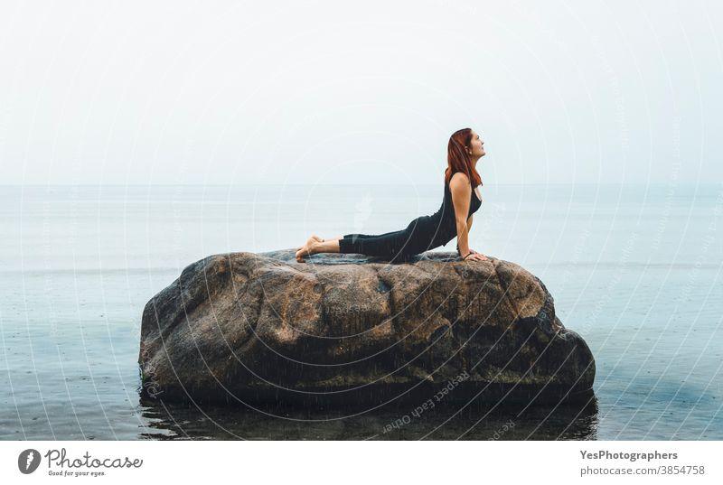Young woman practicing yoga, at sea, in rain. Redhead girl meditating on a rock in the Baltic Sea, Germany 20s Iyengar yoga adult alone baltic sea caucasian