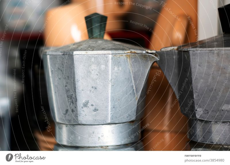 Close-up view of an old coffee pot inside a pantry. moka moka pot coffee maker stainless steel kitchenware espresso espresso maker ruined pour spout handle