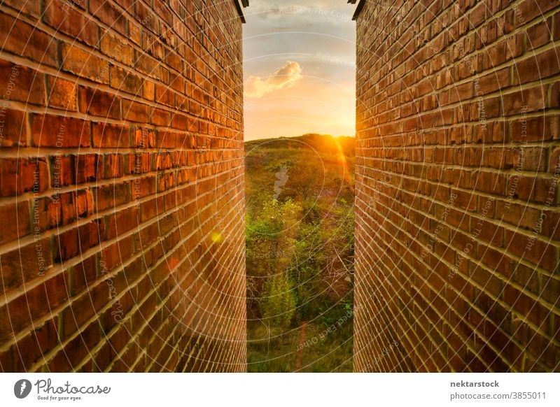 Golden Sunrise and Landscape Between Brick Walls brick landscape narrow sunrise golden opening light at the end of the tunnel rolling landscape concept hope