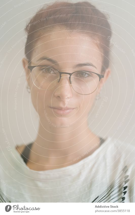 Smart woman looking at camera appearance smirk smart young portrait glasses casual confident individuality female clever eyewear modern model accessory