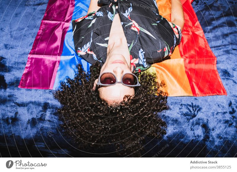 Relaxed female lying on LGBT flag on bed woman equal rainbow homosexual respect tolerance upside down right community gender solidarity same sex discriminate