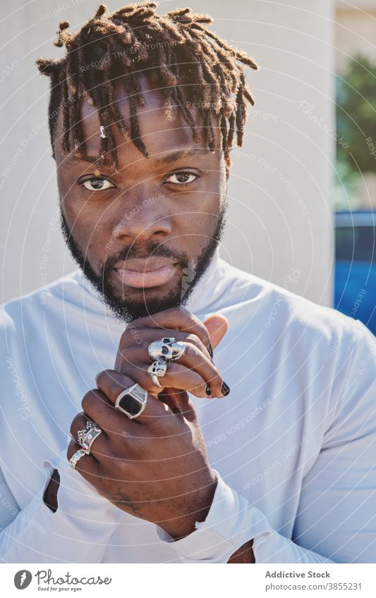 Stylish black man with unusual appearance dreadlocks manicure fancy style hairstyle ring hipster portrait male ethnic african american fashion trendy cool