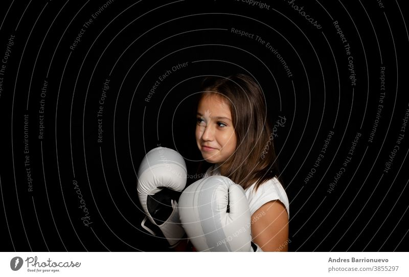 Beautiful little girl with boxing gloves posing funny on black background athletic gesticulate training fit health lady pretty wearing sportive woman female