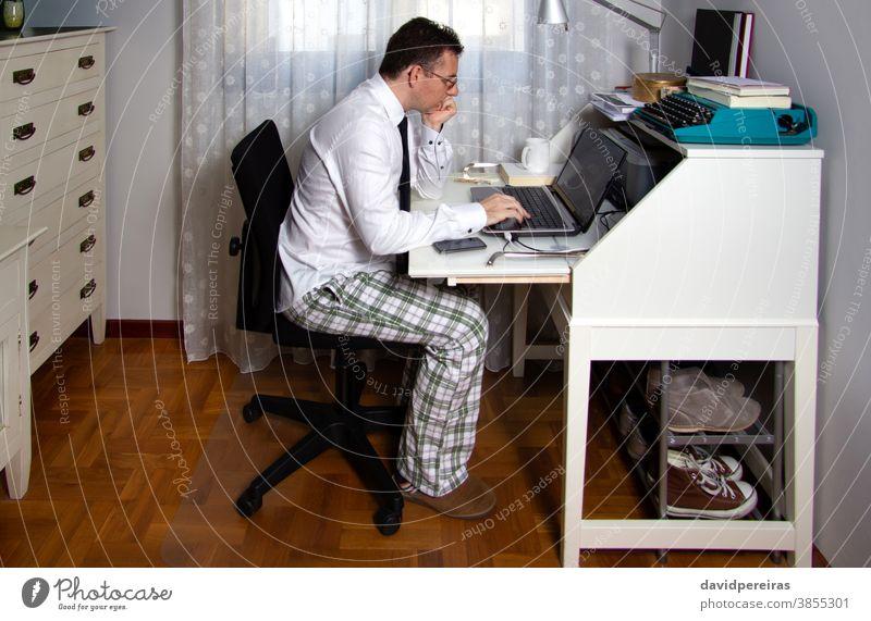 Man teleworking wearing shirt, tie and pajama pants working from home coronavirus epidemic quarantine telecommuting social distancing laptop internet technology