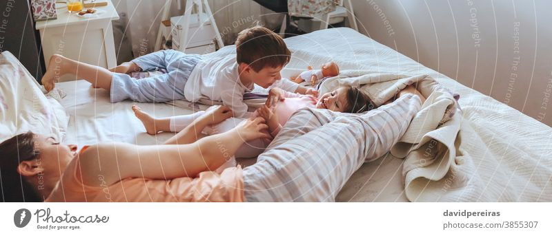 Relaxed mother and sons playing over the bed covid-19 confinement family child panoramic panorama laugh cheerful smiling smile happiness coronavirus